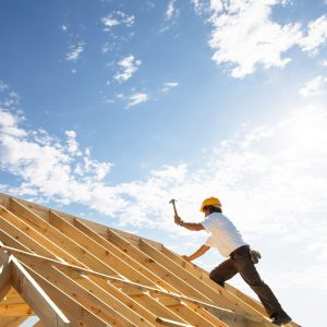 roofer carpenter working on roof structure on building site